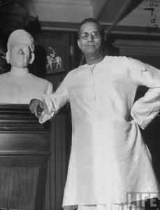 Indian Industrialist G. D. Birla (L) backer & benefactor to Hindu ldr. Mohandas Gandhi, posing next to bust of his father, the founder of the Birla firm, at his palacial home 1946